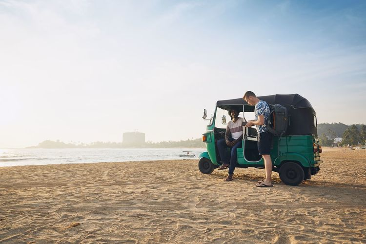 Men talking by rickshaw at beach