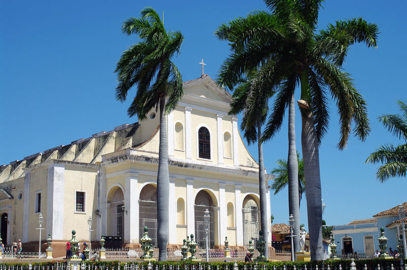 Architecture Catholic Church Cuba Trinidad Architecture Belief Blue Building Building Exterior Built Structure Caribbean Clear Sky Colonial Architecture Colonization Day Low Angle View Nature Outdoors Palm Tree Place Of Worship Plant Religion Sky Spirituality Tourism Travel Destinations Tree Tropical Climate