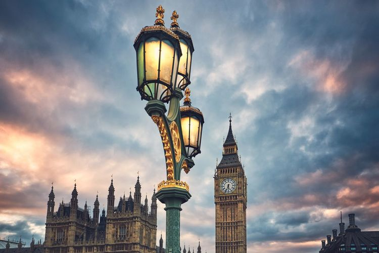Low Angle View Of Illuminated Street Light With Big Ben And Houses Of Parliament Against Cloudy Sky