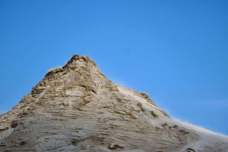 Low angle view of rock formation against clear blue sky on the beach