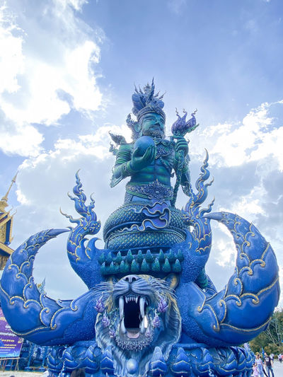 Low angle view of statue against blue sky