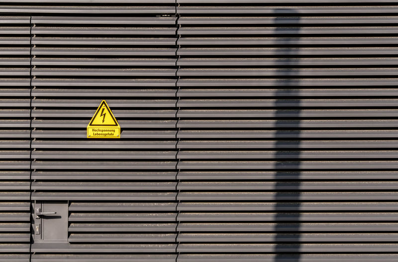 Warning sign on wall during sunny day