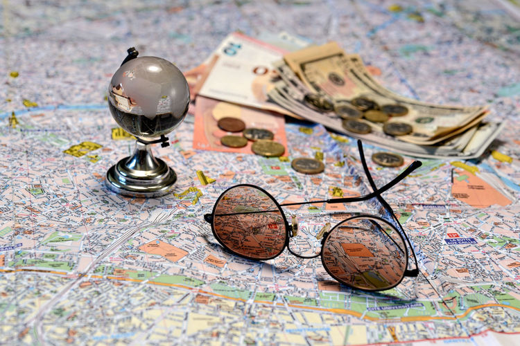 Sunglasses, a glass globe and money on a tourist map background. Tourism concept. Dollar Money Cash Savings Banking Finance Bill Currency Wealth Background Banknote Bussiness Profit Green Close-up USD Exchange Loan  Paper Sign Payment Pay Stack Number Textured  Abstract Earnings Symbol Capital Assets Sunglasses Map Tourism Euro Coins Travel Destination Concept Glass Globe Glass - Material Direction World Map Globe - Man Made Object No People Global Business Guidance Physical Geography Indoors  Journey Adventure Planning Vacations Discovery Selective Focus Business Multi Colored Holiday Antique Topography Road Trip