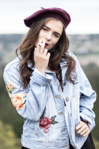 Portrait of young woman smoking while standing outdoors