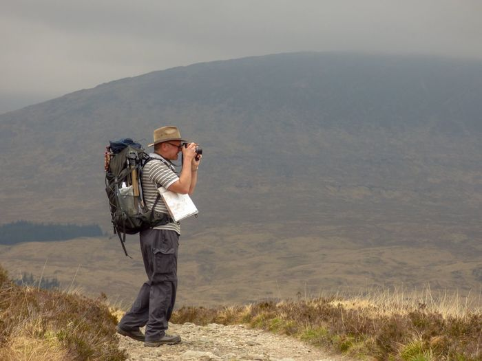 Taking a photo on a misty morning Rannoch Moor Moor  West Highland Way Mist Rucksack Photographer Photography One Person Mountain Adult Clothing Nature Scenics - Nature Full Length Standing Environment Hat Beauty In Nature Landscape Leisure Activity Contemplation