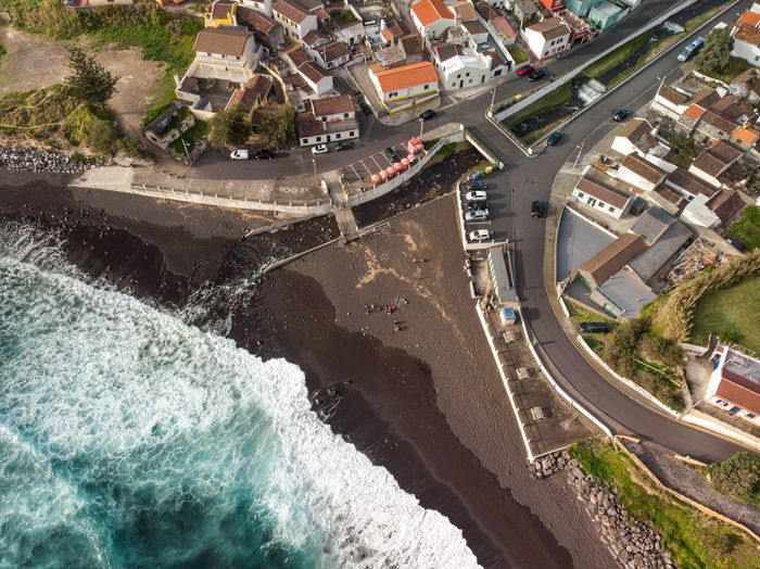 Aerial view of blue ocean water crashing into the black sand beach
