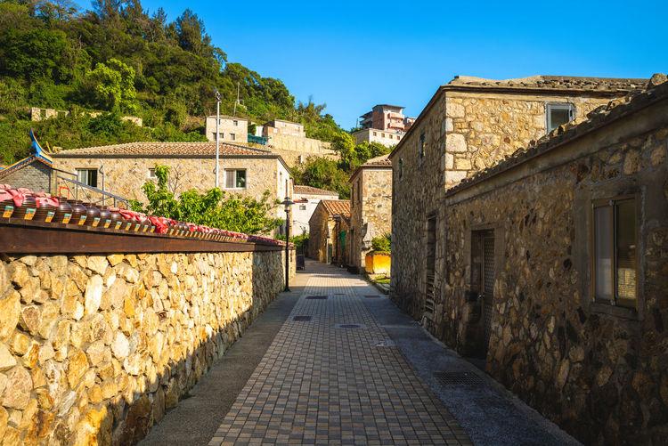 Street amidst buildings against blue sky