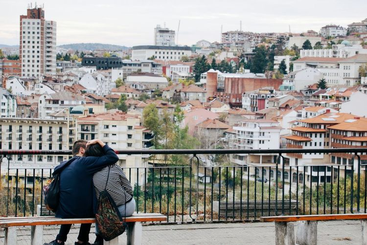 Rear view of couple sitting on bench against city