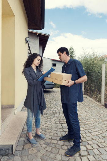 Woman Signing On Clipboard By Delivery Man Against House