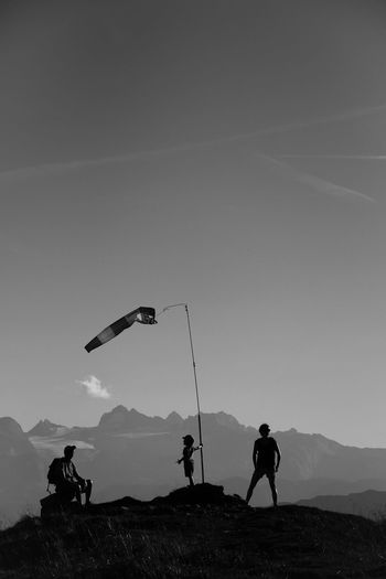 People standing around windsock on mountains against sky