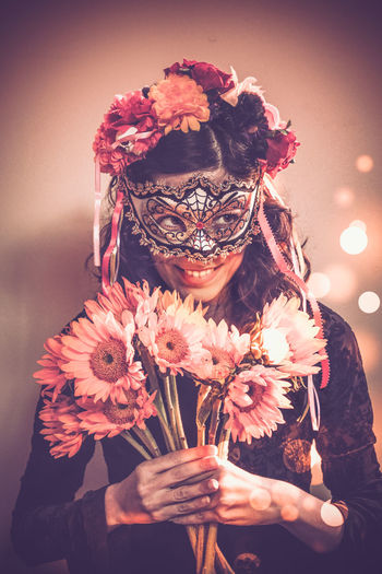 Young man wearing masquerade mask while holding flowers against wall