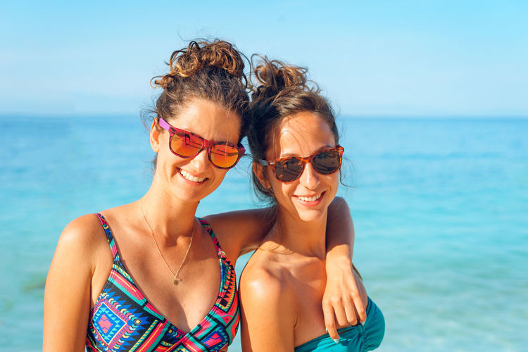 Portrait of smiling woman with sunglasses against sea