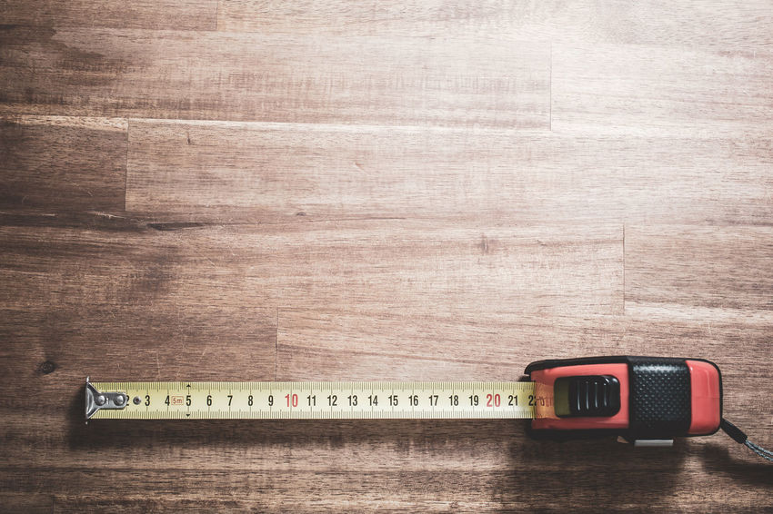 A Solid Measuring Tape With Pulled Out Scale Lying At The Bottom Of A Wooden Table, Top Down View Flexible Measuring Tape Metric Soft Wood Centimeter Close-up Cm Lying Down Macro Measure Measurement Meter Number Pulled Solid Table Tape Tool Toolkit Wood - Material Yellow