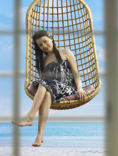 Close-Up Portrait Of Smiling Young Woman Sitting On Swing At Beach