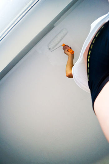 Low angle view of woman painting ceiling at home