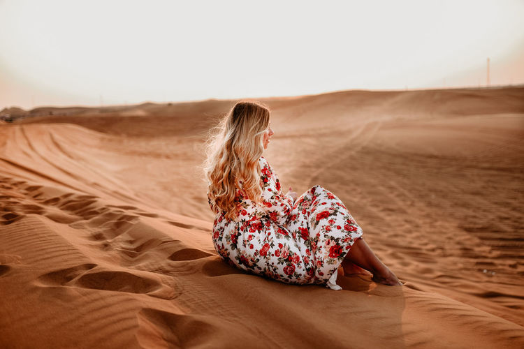 sitting on sand dune in desert.