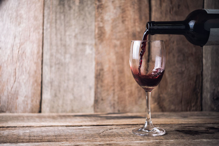 Close-Up Of Wine Pouting In Wineglass On Wooden Table