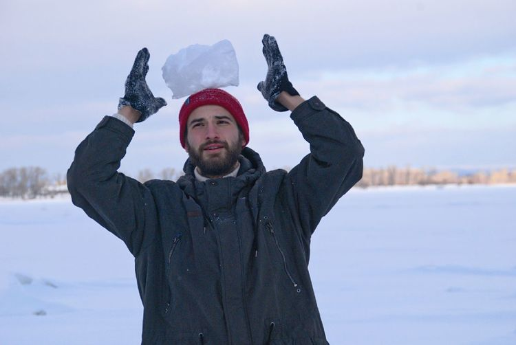 Portrait Of Young Man Balancing Ice On Head Outdoors