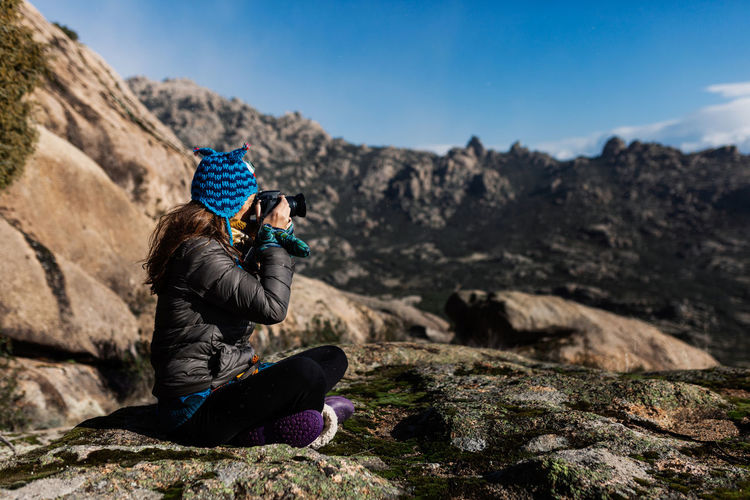 Man photographing rock on mountain against sky