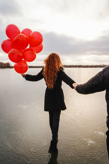 Rear view of woman holding balloons standing with boyfriend at beach