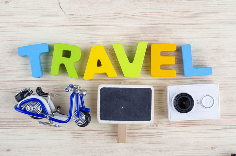 top view vacation and holiday concept word TRAVEL with accessories on wooden background Indoors  Still Life Text Wood - Material Table Directly Above Capital Letter Childhood Letter High Angle View Toy Alphabet Western Script Multi Colored Communication Plastic Arrangement Education Variation