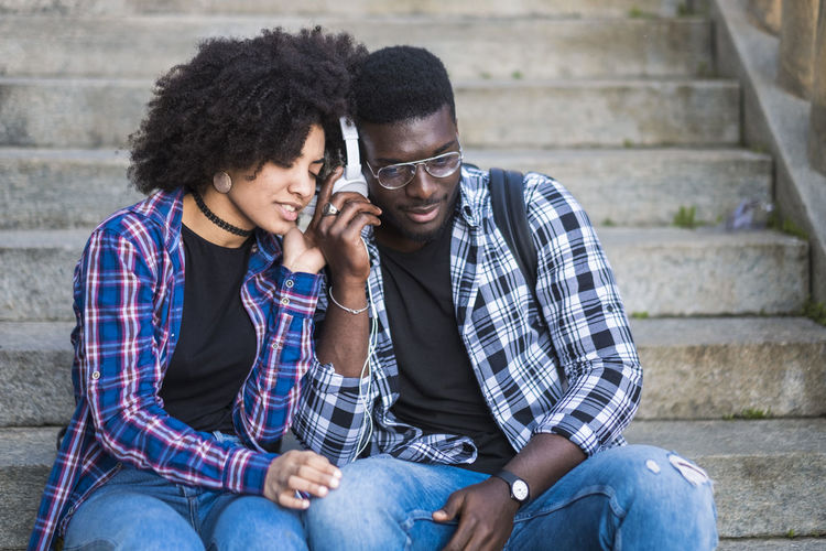 Young couple listening music from one shared headphones in friendship and relationship - feeling and love for girl and boy - first date concept - diversity with afro american people with hipster style Two People Togetherness Sitting Young Adult Staircase Young Women Bonding Architecture Young Men Women Smiling Emotion Three Quarter Length Front View Couple - Relationship Adult Happiness Heterosexual Couple Positive Emotion Steps And Staircases Hair Outdoors Hairstyle Checked Shirt Enjoying Life Millennial Beautiful People Music Listening To Music Eyeglasses  20-24 Years Sitting Sunlight City Life Student Afro Hair Hipster - Person Friendship Enjoyment Technology Freedom Jeans Casual Clothing Relaxation Leisure Activity Arms Raised Hand Happiness Boyfriend Girlfriend