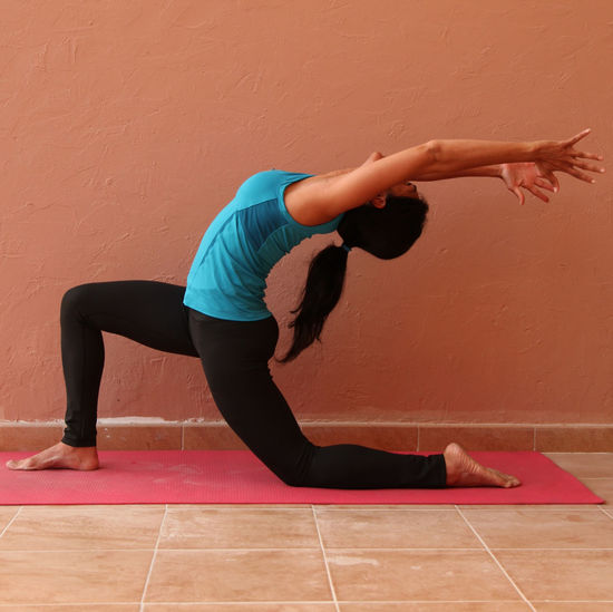 Young Woman Practicing Yoga On Mat Against Wall