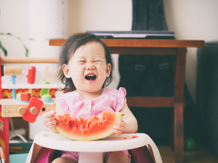 Baby girl holding watermelon while sitting on high chair at home