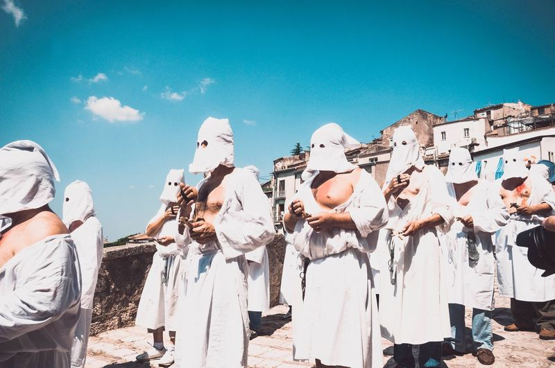 People wearing traditional clothes in parade against clear sky