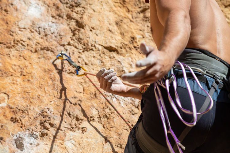 Midsection of man climbing on rocky mountain during sunny day