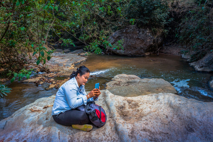 Woman Using Mobile Phone While Sitting On Rock In Forest