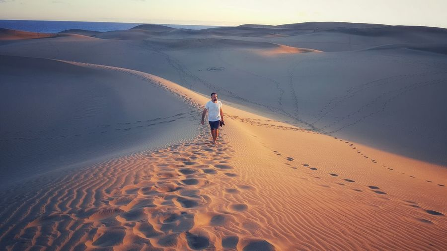 High angle view of man walking on sand dune in desert
