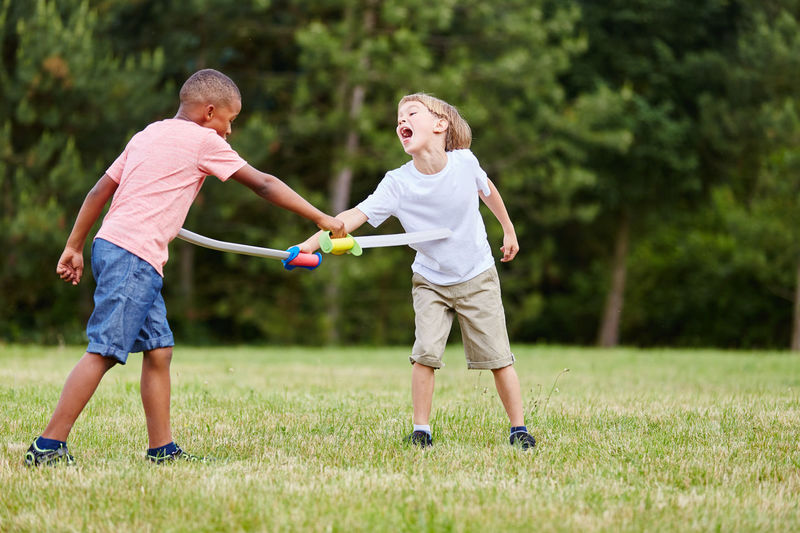 Friends playing with plastic swords on field in park