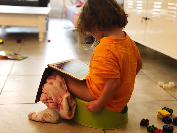 Girl Using Digital Tablet While Sitting On Toilet Bowl At Home