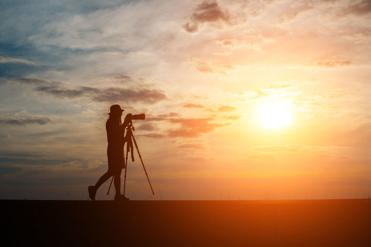 Beauty In Nature Camera - Photographic Equipment Cloud - Sky Digital Camera Full Length Land Nature Occupation One Person Orange Color Outdoors Photographer Photographic Equipment Photography Themes Real People Scenics - Nature Silhouette Sky Standing Sun Sunset Technology Tripod