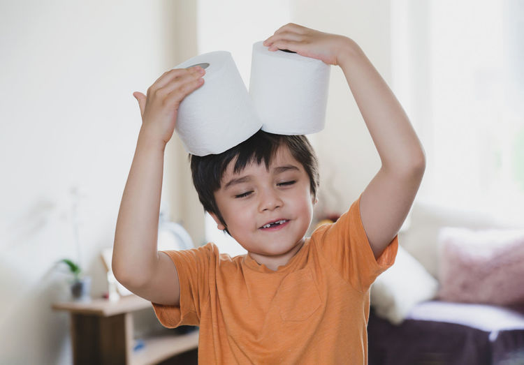Cute boy holding toilet paper roll at on head at home