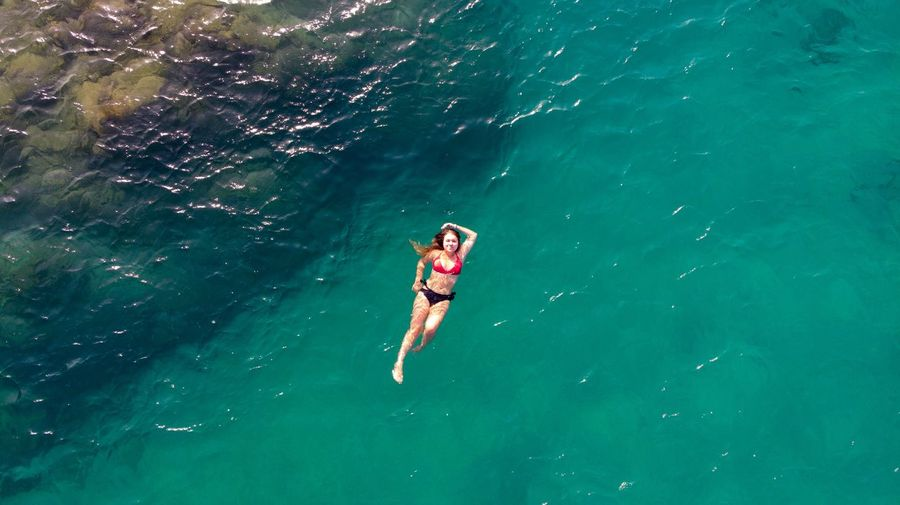 High angle view of bikini woman swimming in sea