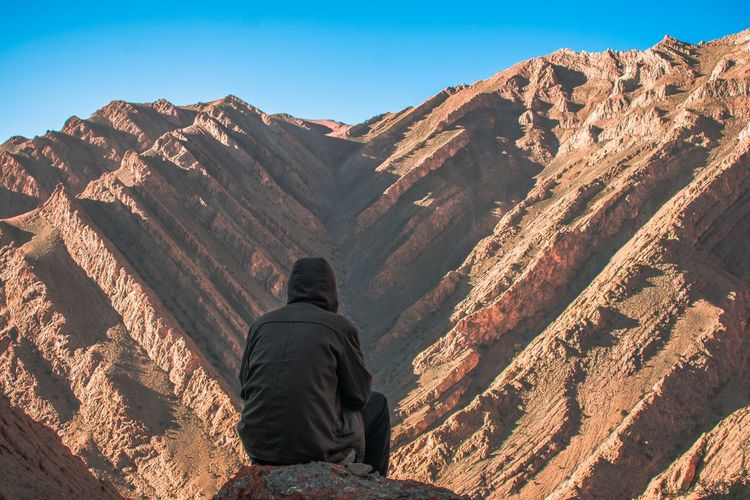 Rear view of man sitting against rocky mountains