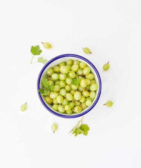 A bowlful of gooseberries on a white background from above. Abundance Bowl Choice Close-up Composition Directly Above Food Food And Drink Freshness Fruit Gooseberries Gooseberry Green Healthy Eating Healthy Lifestyle Indoors  Large Group Of Objects Organic Ripe Sour Still Life Table Temptation Variation Yellow Crafted Beauty