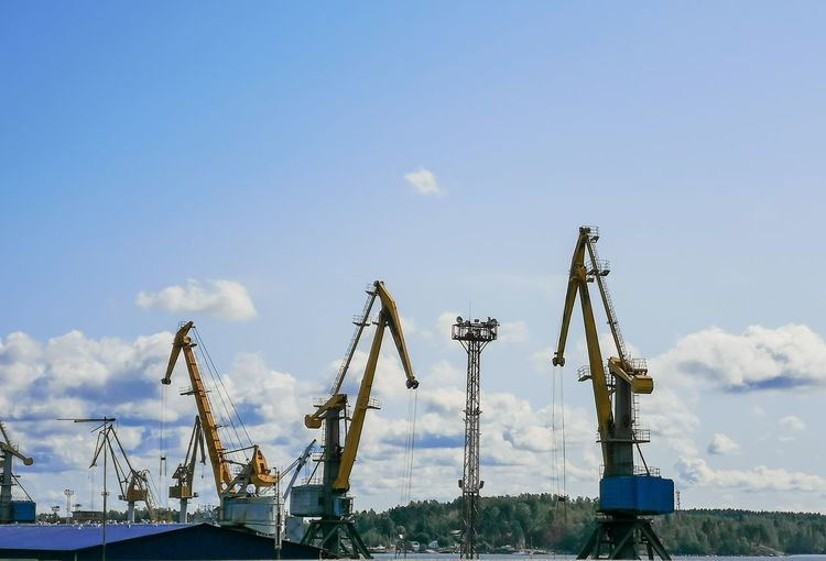 Cranes at harbor against sky