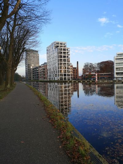 River by buildings in city against sky