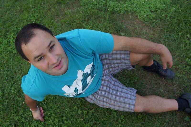High Angle Portrait Of Man Sitting On Grassy Field In Yard