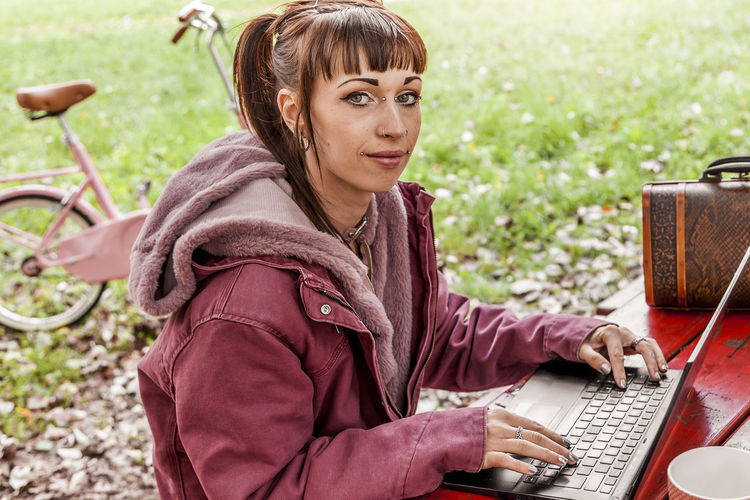 young woman studying with computer sitting on a wooden table in the park among the autumn leaves Females Women Portrait Millennials Technology 20-29 Years Young Adult Laptop Computer Wireless Technology One Person Using Laptop Connection Casual Clothing Caucasian Ethnicity Text Messaging Piercing Social Issues People Park Outdoors Leaves