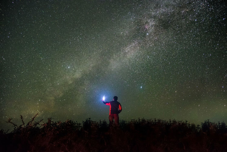 Rear view of man with illuminated flashlight standing against star field