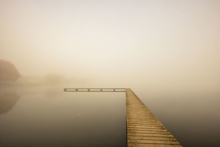 Pier over lake against sky during foggy weather