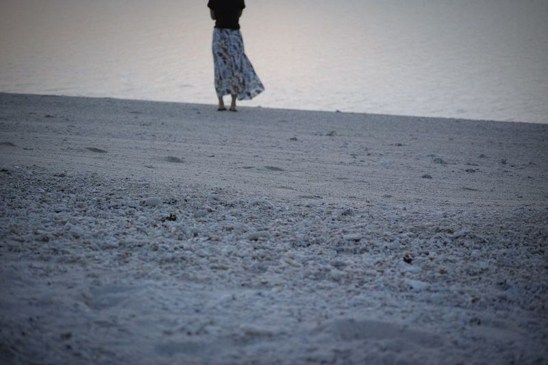 Low section of woman standing at beach