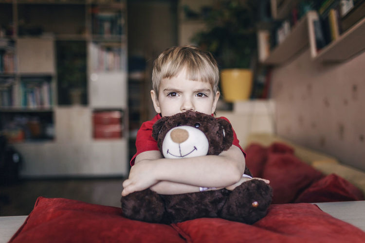 Portrait of boy with stuffed toy at home