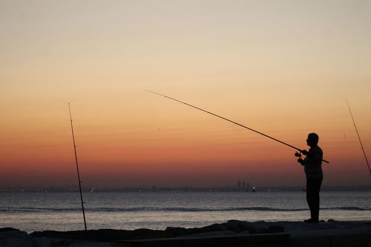 Man fishing in sea against sky during sunset
