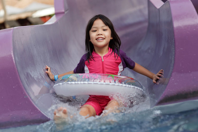 Portrait Of Happy Girl Sliding Down In Water Slide At Water Park