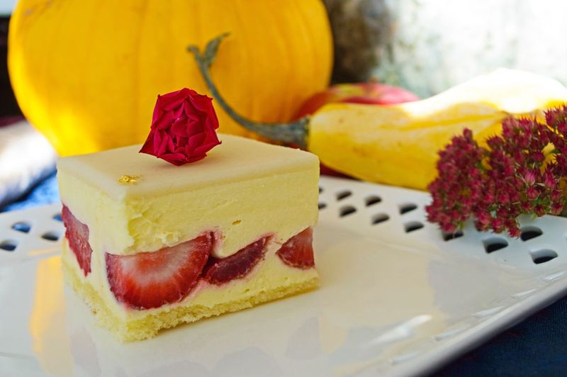 Close-Up Of Strawberry Cream Cake With Pumpkin In Background